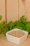 Bowl with sorghum with basil. Sorghum grains with basil on wood Stock Photos