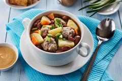Bowl of soup with beans, meatballs and spring onion Stock Image