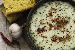 Bowl of soup with bread, garlic and red peppers Royalty Free Stock Photography
