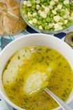 Bowl of soup with noodles and plate of vegetables Stock Photo