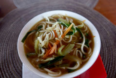 A bowl of soup with noodles and vegetables on a round napkin. Nepal Royalty Free Stock Photography