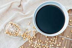 A bowl of soy sauce and sprinkled soybeans royalty free stock image