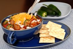 Bowl of spicey chili and crackers with jalapeno peppers Royalty Free Stock Photos