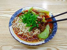 A bowl of spicy Sichuan noodles with beef with chive and greens royalty free stock photography