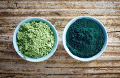 Bowl of spirulina algae powder and wheat sprout powder on wooden Stock Images