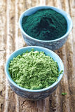 Bowl of spirulina algae powder and wheat sprout powder on wooden Royalty Free Stock Image