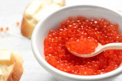 Bowl and spoon with red caviar. Closeup stock photo