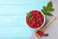 Bowl and spoon with ripe raspberries on wooden table, top view. Bowl and spoon with ripe aromatic raspberries on wooden table, top view Royalty Free Stock Images