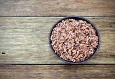 Bowl of steam Red Cargo Rice on wood Stock Photography