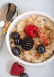 Bowl of steel cut oats served with fresh fruit and honey Stock Photography