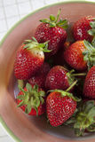 Bowl of strawberries. Bowl of red strawberries on a picnic table cloth Stock Image