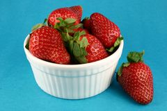Bowl of Strawberries. Against blue background Stock Photo