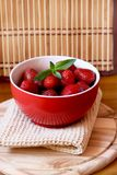Bowl of strawberries. Red bowl with sweet and delicious strawberries with a sprig of mint Stock Images