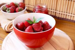 Bowl of strawberries. Red bowl with sweet and delicious strawberries with a sprig of mint royalty free stock photo