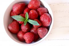 Bowl of strawberries. Red bowl with sweet and delicious strawberries with a sprig of mint stock photo