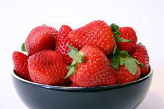 Bowl of strawberries. A black bowl full of strawberries stock photo