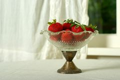 Bowl of strawberries. Vintage glass bowl with strawberries; off white table cloth and curtain in casual kitchen setting royalty free stock images