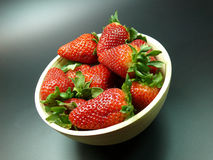 Bowl of strawberries. Bowl of red ripe strawberries.  Against a gray studio background Royalty Free Stock Photo