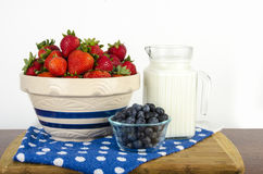 Bowl of Strawberries, blueberries and Milk Stock Images