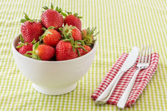A bowl of strawberries and flatware royalty free stock photo