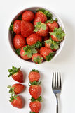 Bowl with strawberries. High-angle shot of a white ceramic bowl full appetizing strawberries, a fork and some other strawberries on a white surface Royalty Free Stock Image