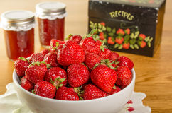 Bowl of strawberries and jars of jam Royalty Free Stock Images
