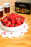 Bowl of strawberries and jars of jam Stock Photography