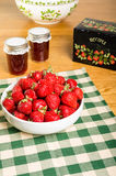 Bowl of strawberries and jars of jam Stock Images