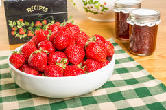 Bowl of strawberries and jars of jam Royalty Free Stock Photo