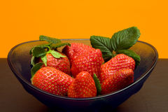 Bowl With Strawberries On Orange Background stock images