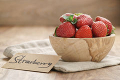 Bowl with strawberries with paper card on napkin on wwood table Royalty Free Stock Image