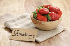 Bowl with strawberries with paper card on napkin on wwood table Royalty Free Stock Photo