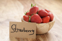 Bowl with strawberries with paper card on wood table Royalty Free Stock Photography