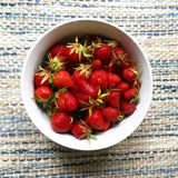 Bowl of strawberries. Bowl of red wild strawberries overhead Royalty Free Stock Image