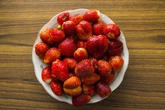 Bowl of strawberries top view. On wooden table Stock Photos