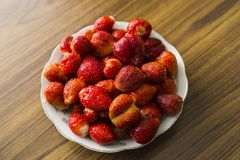 Bowl of strawberries top view. On wooden table royalty free stock photo