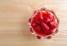 Bowl of strawberries on wood table Royalty Free Stock Images