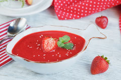 A bowl of strawberry soup gazpacho with mint. On white wooden background Royalty Free Stock Photos