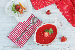 A bowl of strawberry soup gazpacho with mint. On white wooden background Stock Image