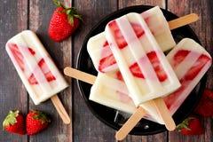 Bowl of strawberry vanilla yogurt popsicles on dark wood Royalty Free Stock Photography