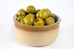Bowl of stuffed olives. A small bowl of green olives stuffed with red pepper isolated on a white background Royalty Free Stock Photo