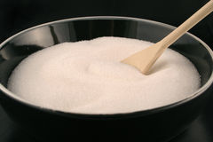 Bowl of sugar. A black bowl of plain white sugar with a wooden spoon in it stock images