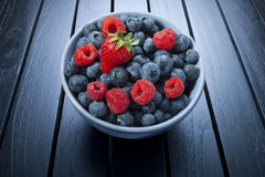 Bowl Of Summer Berries. A bowl of fresh summer berries on a black wood background Stock Photos