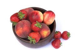 Bowl of summer fruits. Wooden bowl of summer fruits, strawberries, peaches and nectarines Stock Photography