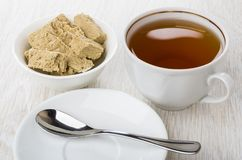 Bowl with sunflower halva, tea, teaspoon on saucer on table Royalty Free Stock Image