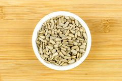 Bowl of sunflower seeds against wooden background Stock Images
