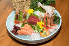 Bowl of sushi with shrimp, tuna, salmon, shell, oyster and sea g. Rape on wooden table deliciously Royalty Free Stock Photography