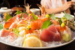 Bowl of sushi  with tuna salmon oyster and shrimp. On wooden table Royalty Free Stock Photography