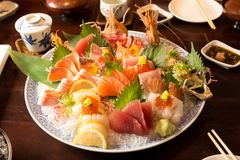 Bowl of sushi  with tuna salmon oyster and shrimp. On wooden table Stock Images