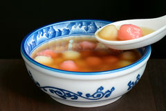 Bowl of sweet Chinese tangyuan dessert being eaten with a spoon Stock Photo